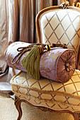 Quaste und Kissenrolle auf einem Barockstuhl mit Rautenmuster