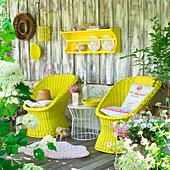 Gelb gestrichene Korbstühle und Accessoires auf der Terrasse
