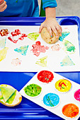 Child making colourful potato prints