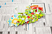 Large jigsaw pieces spread out on newspaper