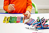 Child arranging coloured wax crayons on canvas