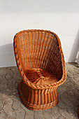 Wicker easy chair against white wall in courtyard