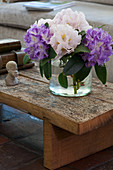 Vase of purple and white rhododendrons on rustic wooden coffee table