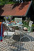 Gedeckter Gartentisch auf gepflasterter Terrasse im Sommer