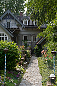 Paved path leading through summery garden to Art Nouveau house