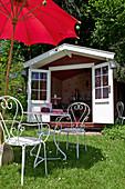 French garden furniture below parasol outside summerhouse