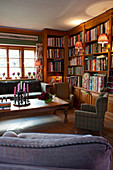Fitted bookcases and various seating in living room