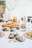 Mit Pouring in Naturtönen bemalte Kieselsteine auf gedecktem Tisch