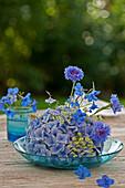 Various flowers arranged in hydrangea flower head in glass dish