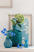 Pale green hydrangea in vintage glass vase and delphinium in turquoise vase