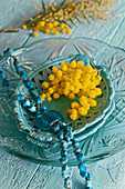 Turquoise necklace and mimosa flowers on ceramic dish