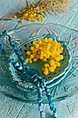 Türkisfarbene Kette und Mimosen auf Keramikschale