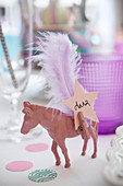 Pink-painted horse with peg, feather and name card