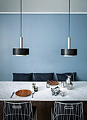 Designer lamps above dining table in front of pale blue wall