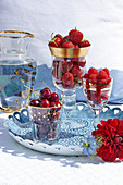 Glasses with sweet cherries, strawberries and raspberries on a tray