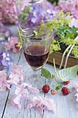 Ein Glas Himbeerlikör mit Hortensien und Himbeeren