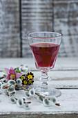 Ein Glas Aroniasaft, Küchenschelle (Pulsatilla vulgaris) Weidenkätzchen und Primeln