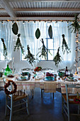 Festively decorated dining table below fairy lights and suspended bunches of leafy branches