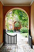 Open gate in arched passageway leading into courtyard
