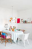 Rattanstühle am Tisch im Esszimmer in Weiß mit bunten Farbakzenten