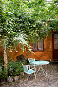 Table and chairs under birch in paved courtyard of house