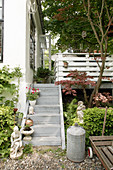 Steps leading to terrace and sculptures in summery garden