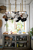 Hanging pot rack above glass-fronted cabinet