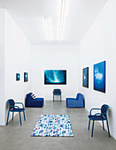 Chairs with woven seats and backs and modular outdoor armchairs in shades of blue in exhibition space