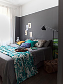 Turquoise blanket with tropical motif on grey double bed