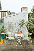 Green garden chairs at folding table on terrace against outside wall of house