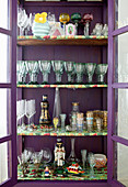 Old glasses in purple, glass-fronted cabinet with multi-coloured shelves