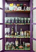 Alte Gläser in einem violetten Vitrinenschrank mit bunten Böden