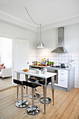 Barstools at high, modern table in simple, classic kitchen-dining room