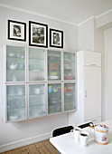 Crockery in wall-mounted cabinets with frosted glass doors in kitchen