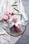 Gift wrapped in fabric in metal rink with pink carnations