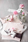 Pastel arrangement: envelopes tied with satin ribbons and pink carnations