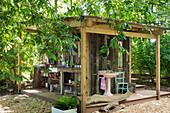Outdoor-Küche und Outdoor-Bad an der Fassade einer kleinen Holzhütte