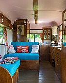 Wooden furnishings and blue upholstery in old caravan