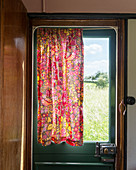 Red, floral curtain on door of old caravan