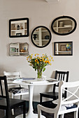 Arrangement of mirrors on wall above dining table and various chairs