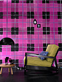 Armchair and side table in front of wall with wallpaper in oversized pink-and-black tartan pattern