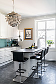 Black barstools at counter and designer lampshade in modern kitchen