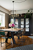 Dining table with rustic wooden top and vintage chairs in front of glass-fronted cabinet