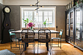 Dining table and vintage chairs on wooden floor and in front of window