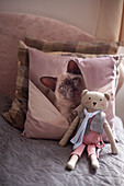 Handmade teddy bear and scatter cushion with cat motif on bed
