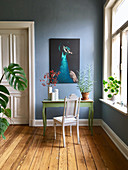 Antique chair at green console table against blue wall in period building