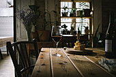 Bottle and glass of red wine and cheeseboard on rustic wooden table