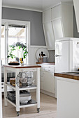 Serving trolley used as island counter in white country-house kitchen