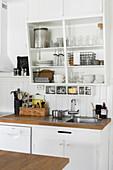 Crockery and glasses on slanted shelves above sink