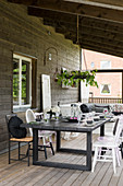 Set dining table on roofed terrace of wooden house